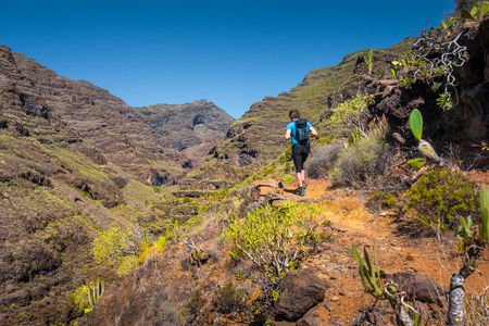 Beautiful panorama view of male tourist hiking on a trail in idyllic exotic scenery on a scenic sunny day with blue sky and clouds in summer, Canary Islands, Spain