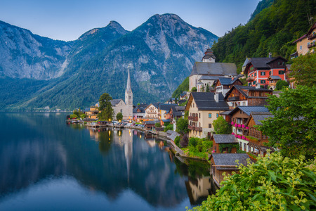 Scenic picture-postcard view of famous historic Hallstatt mountain village with Hallstattersee in the Austrian Alps in mystic twilight during blue hour at dawn in summer, Salzkammergut region, Austria Stock Photo