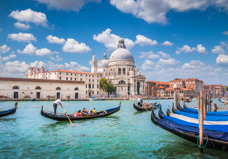 Beautiful view of traditional Gondolas on Canal Grande with historic Basilica di Santa Maria della Salute in the background on a sunny day in Venice, Italy Stock Photo