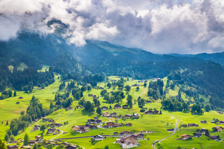 Beautiful view of idyllic mountain scenery in the Alps with famous Eiger and Jungfrau summits and chalet in fresh green meadows of blooming flowers in summer, Grindelwald, Canton of Bern, Switzerland