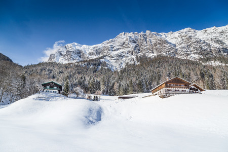 Panoramic view of beautiful winter wonderland mountain scenery in the Alps with traditional mountain chalets on a cold sunny day with blue sky and clouds
