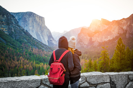 Romantic view of a young couple lying in arms  while enjoying the scenic landscape of Yosemite Valley with El Capitan in beautiful morning light at sunrise from famous Tunnel View, California, USA