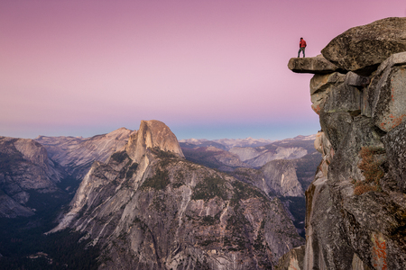 A fearless male hiker is standing on an overhanging rock at Glacier Point enjoying the breathtaking view towards famous Half Dome in beautiful post sunset twilight in summer, Yosemite National Park, California Standard-Bild