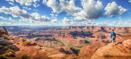 Panoramic view of young hiker standing on a cliff in in scenic Dead Horse Point State Park enjoying the view on a beautiful sunny day with blue sky and dramatic clouds in summer, Utah, USA Archivio Fotografico - 96513640