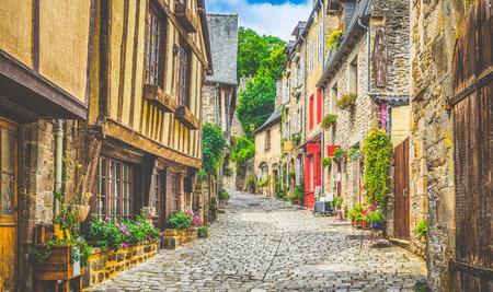 歴史的な伝統的な家と夏の青空と雲とヨーロッパの旧市街の石畳の通りを持つ風光明媚な狭い路地の美しい景色は、レトロなヴィンテージグランジ