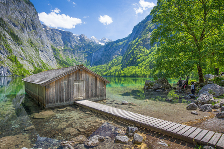 Beautiful view of traditional wooden boat house at the shores of famous Lake Obersee in scenic Nationalpark Berchtesgadener Land on a sunny day in summer, Bavaria, Germany