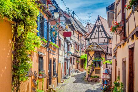 Encantadora escena callejera con coloridas casas en la histórica ciudad de Eguisheim en un hermoso día soleado con cielo azul y nubes en verano, Alsacia, Francia Foto de archivo