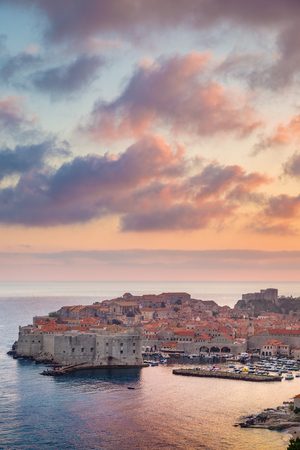 Panoramic aerial view of the historic town of Dubrovnik, one of the most famous tourist destinations in the Mediterranean Sea, in beautiful golden evening light at sunset with clouds in summer, Dalmatia, Croatia