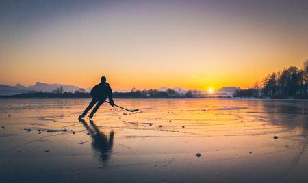 Malowniczy panoramiczny widok sylwetki młodego hokeisty jeżdżącego na łyżwach po zamarzniętym jeziorze z niesamowitymi refleksami w pięknym złotym wieczornym świetle o zachodzie słońca w zimie