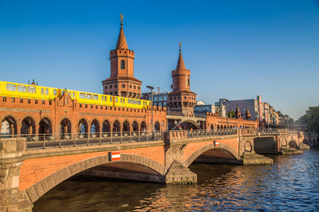 Classic panoramic view of famous Oberbaum Bridge with historic Berliner U-Bahn crossing the Spree river on a beautiful sunny day with blue sky in summer, Berlin, Germany Banque d'images