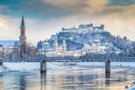 Classic view of the historic city of Salzburg with famous Hohensalzburg Fortress and Salzach river in beautiful golden evening light at sunset in winter, Austria