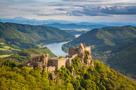 Classic aerial view of historic Aggstein castle ruin with famous Danube river in the background in beautiful golden evening light at sunset in summer, Wachau valley, Lower Austria region, Austria