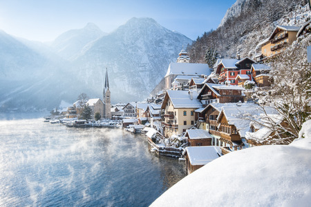 Classic postcard view of famous Hallstatt lakeside town in the Alps on a beautiful cold sunny day with blue sky and clouds at sunrise in winter, Salzkammergut region, Austria 報道画像