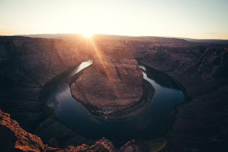 Classic wide-angle view of famous Horseshoe Bend, a horseshoe-shaped meander of the Colorado River located near the town of Page, in beautiful golden evening light at sunset in summer, Arizona, USA 版權商用圖片