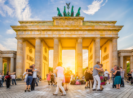 People dancing in front of famous Brandenburg Gate, a symbol for peace and unity and historic landmark, in golden evening light at sunset with blue sky in summer, Berlin, Germany