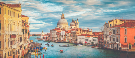 Classic panoramic view of famous Canal Grande with scenic Basilica di Santa Maria della Salute in beautiful golden evening light at sunset with retro vintage filter effect, Venice, Italy Stock Photo