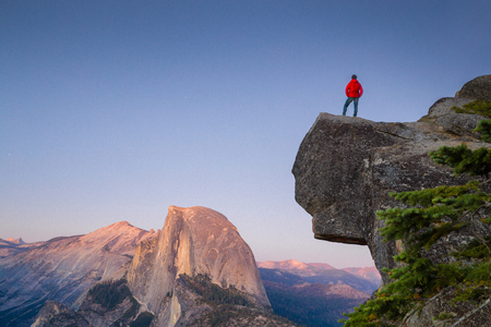 A fearless hiker is standing on an overhanging rock enjoying the view towards famous Half Dome at Glacier Point overlook in beautiful post sunset twilight, Yosemite National Park, California, USA 版權商用圖片