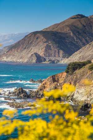 Scenic view of the rugged coastline of Big Sur with Santa Lucia Mountains and Big Creek Bridge along famous Highway 1 in beautiful golden evening light at sunset in summer, California Central Coast, USA