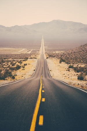 Classic panorama view of an endless straight road running through the barren scenery of the American Southwest with extreme heat haze on a beautiful sunny day with blue sky in summer 스톡 콘텐츠