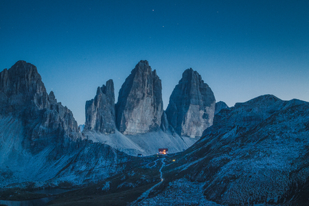 Beautiful view of famous Tre Cime di Lavaredo mountains in the Dolomites mountain range with famous Rifugio Antonio Locatelli alpine hut on a clear starry night in summer, South Tyrol, Italy Stock Photo