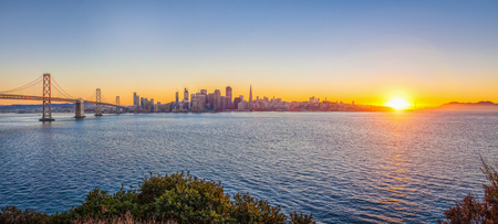 Classic panoramic view of San Francisco skyline with famous Oakland Bay Bridge illuminated in beautiful golden evening light at sunset in summer, San Francisco Bay Area, California, USA
