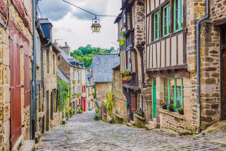 Beautiful view of scenic narrow alley with historic traditional houses and cobbled street in an old town in Europe with blue sky and clouds in summer with retro vintage filter effect