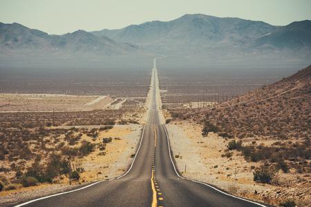 夏の青空の美しい晴れた日に極端な熱ヘイズでアメリカ南西部の不毛な風景を走る無限のまっすぐな道の古典的なパノラマビュー
