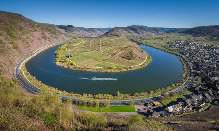 Panoramic view of ship on famous Moselle river at Moselschleife with the historic town of Bremm on a beautiful sunny day with blue sky in springtime, Rheinland-Pfalz, Germany
