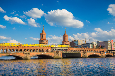 Classic panoramic view of famous Oberbaum Bridge with historic Berliner U-Bahn crossing the Spree river on a beautiful sunny day with blue sky and clouds in summer, Berlin, Germany