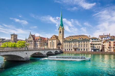 Historisches Stadtzentrum von Zürich mit berühmter Fraumünster-Kirche und Ausflugsboot auf Fluss Limmat, Kanton Zürich, die Schweiz