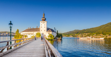 Panoramic view of famous Schloss Ort with traditional paddle steamer ship at Lake Traunsee in beautiful golden evening light at sunset, Gmunden, Salzkammergut region, Austria