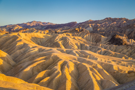 Scenic panoramic view of amazing sandstone formations at famous Zabriskie Point viewpoint in beautiful golden evening light at sunset, Death Valley National Park, California, USA Banco de Imagens - 96036924
