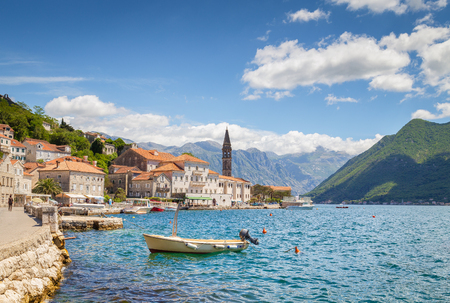 Classic panorama view of the historic town of Perast located at world-famous Bay of Kotor on a beautiful sunny day with blue sky and clouds in summer, Montenegro, southern Europe.