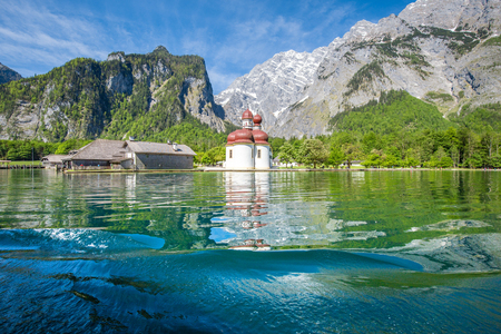 Classic panoramic view of Lake Konigssee with world famous Sankt Bartholomae pilgrimage church and Watzmann mountain on a beautiful sunny day in summer, Berchtesgadener Land, Bavaria, Germany 스톡 콘텐츠 - 96698370