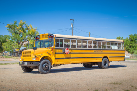 Panorama view of classic tradtional yellow school bus standing on a parking lot on a beautiful sunny day with blue sky in summer in North America