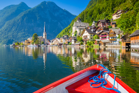 Classic postcard view of famous Hallstatt lakeside town in the Alps with traditional boat in morning light on a beautiful sunny day in summer, Salzkammergut region, Austria