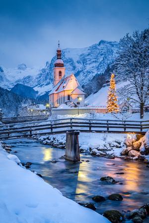 Schöne Dämmerungsansicht der Sankt Sebastian-Wallfahrtskirche mit dem verzierten Weihnachtsbaum belichtet während der blauen Stunde an der Dämmerung im Winter, Ramsau, Nationalpark Berchtesgadener Land, Bayern, Deutschland