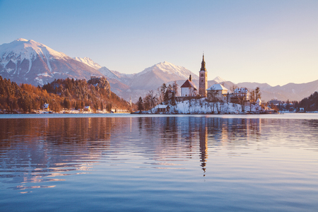 Panoramic view of famous Bled Island (Blejski otok) at scenic Lake Bled with Bled Castle (Blejski grad) and Julian Alps in the background in beautiful golden morning light at sunrise in winter, Slovenia.