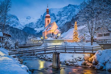 Piękny widok zmierzchu kościoła pielgrzymkowego Sankt Sebastian z ozdobioną choinką oświetloną podczas niebieskiej godziny o zmierzchu w zimie, Ramsau, Nationalpark Berchtesgadener Land, Bawaria, Niemcy