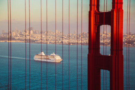 Beautiful panorama view of cruise ship approaching famous Golden Gate Bridge with the skyline of San Francisco in the background in beautiful golden evening light at sunset in summer, California, USA Stock Photo