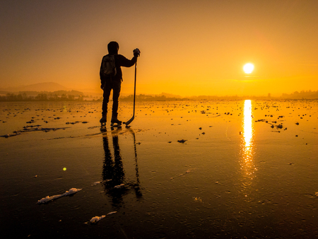 Scenic panoramic view of the silhouette of a young hockey player standing on a frozen lake with amazing reflections in beautiful golden evening light at sunset in winter Reklamní fotografie