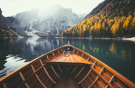 Scenic view of traditional wooden rowing boat gliding on famous Lago di Braies in the Italian Dolomites on a beautiful sunny day in fall with retro vintage filter effect, South Tyrol, Italy Фото со стока