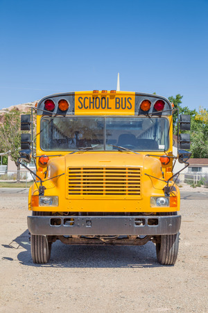 Frontal view of classic tradtional yellow school bus standing on a parking lot on a beautiful sunny day with blue sky in summer in North America Banco de Imagens