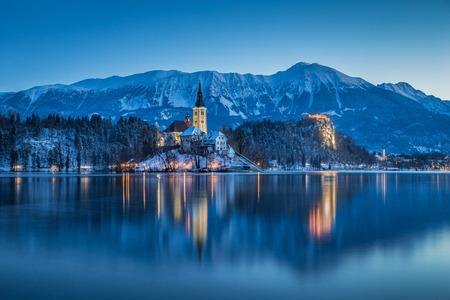 겨울, 슬로베니아에서 새벽 경치 좋은 푸른 시간 동안 백그라운드에서 유명한 블 레드 섬과 역사적인 블 레드 성 블 레드 호수의 아름다운 황혼보기 스톡 콘텐츠 - 97230391