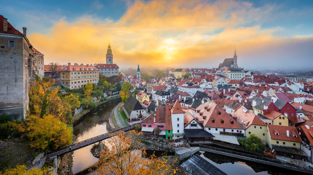 Panoramic view of the historic city of Cesky Krumlov with famous Cesky Krumlov Castle, a UNESCO World Heritage Site since 1992, in beautiful morning light at sunrise with mystic fog in fall, Czech Republic. Redakční