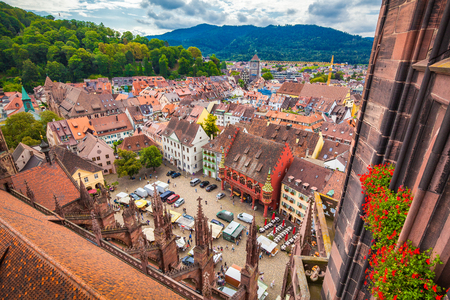 Aerial view of the historic city center of Freiburg im Breisgau from famous Freiburger Minster in beautiful evening light at sunset with blue sky and clouds in summer, Baden-Wurttemberg, Germany
