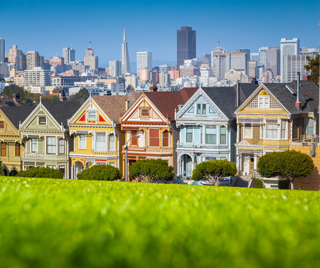 Classic postcard view of famous Painted Ladies, a row of colorful Victorian houses located at scenic Alamo Square, with the skyline of San Francisco in the background on a beautiful sunny day with blue sky in summer Stock Photo