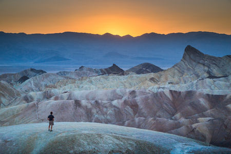 Classic panoramic view of male hiker standing at famous Zabriskie Point viewpoint in beautiful golden evening light at sunset in summer, Death Valley National Park, California, USA