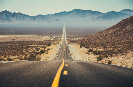 Classic panorama view of an endless straight road running through the barren scenery of the American Southwest with extreme heat haze on a beautiful sunny day with blue sky in summer Stock fotó