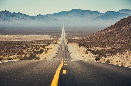 Vista panorámica clásica de una carretera recta interminable que atraviesa el paisaje árido del suroeste de Estados Unidos con una bruma de calor extremo en un hermoso día soleado con cielo azul en verano Foto de archivo